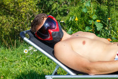 Modern way to protect face from sun rays. Man sunbathing Royalty Free Stock Photos