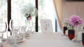 Modern Wedding Decorated Table. Frame with Numbers.  Place setting and card on a table at a wedding reception stock footage