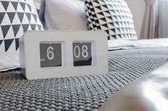 Modern white alarm clock on bed Stock Images