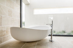 Modern white bathtub. In spacious bathroom with glass wall Stock Images