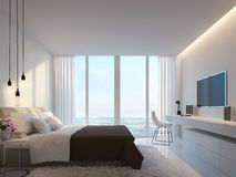 Modern white bedroom with sea view 3d rendering. Image,Decorate wall with hidden warm light,white furniture,There are large windows Looking to beautiful sea Royalty Free Stock Photo