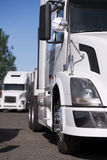 Modern white big rigs semi trucks standing on parking lot. Modern semi trucks with a full-sized long flat bed trailer loaded with cargo are parked on truck stop Royalty Free Stock Images