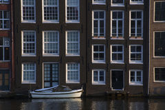 Modern white boat on the water near old buildings. In Amsterdam in the evening Royalty Free Stock Image
