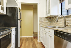 Modern white cabinets and brown mosaic backsplash in apartment Royalty Free Stock Images