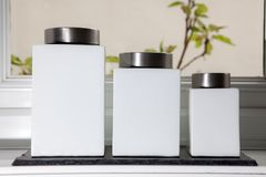 Modern white ceramic food storage containers with label space. Simple square design pottery containers on kitchen window sill Stock Images