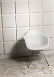Modern white chair against bricked wall Stock Photography