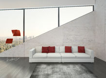 Modern white couch with red pillows against stone wall Stock Photo