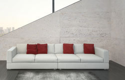 Modern white couch with red pillows against stone wall Royalty Free Stock Photography