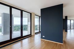 Modern white empty loft apartment interior with parquet floor with black column and panoramic windows, Overlooking the metropolis. City stock photos