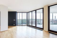 Modern white empty loft apartment interior with parquet floor with black column and panoramic windows, Overlooking the metropolis. City royalty free stock image