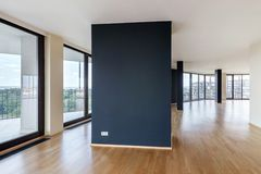 Modern white empty loft apartment interior with parquet floor with black column and panoramic windows, Overlooking the metropolis. City stock photography
