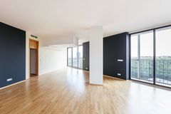 Modern white empty loft apartment interior with parquet floor with black column and panoramic windows, Overlooking the metropolis. City stock image
