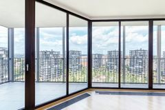 Modern white empty loft apartment interior with parquet floor and panoramic windows, Overlooking the metropolis city.  royalty free stock image