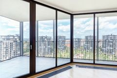 Modern white empty loft apartment interior with parquet floor and panoramic windows, Overlooking the metropolis city.  royalty free stock photography