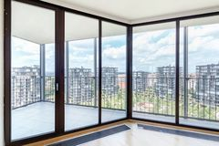 Modern white empty loft apartment interior with parquet floor and panoramic windows, Overlooking the metropolis city.  royalty free stock photo