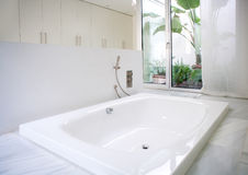 Modern white house bathroom bathtub with courtyard skylight royalty free stock photo