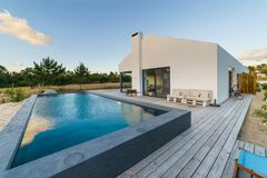 Modern house with garden swimming pool and wooden deck Royalty Free Stock Photography