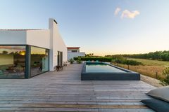 Modern house with garden swimming pool and wooden deck Stock Photos