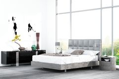 Modern white king-size bed against floor to ceiling window Stock Images