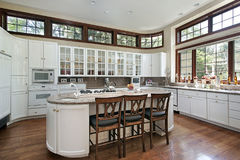 Modern white kitchen. Modern kitchen with white cabinets and multiple windows Royalty Free Stock Photography