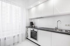 White kitchen with black countertop. Modern, white kitchen with black countertop, sink, cupboards and window stock photos