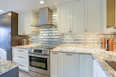 Modern white kitchen design with silver backsplash. White shaker cabinets and gray quartzite countertops Stock Images