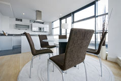 Modern white kitchen with dining area. Modern white kitchen with contemporary dining area and designer furniture Stock Photos