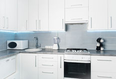 Modern white kitchen frontal view Royalty Free Stock Images