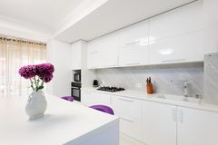 Modern kitchen with dining table and purple chairs Royalty Free Stock Photos