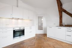 Modern white kitchen in penthouse flat with wooden floor stock photography