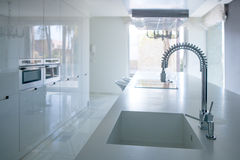 Modern white kitchen perspective with integrated bench. Sink and spring faucet stock image