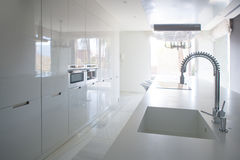 Modern white kitchen perspective with integrated bench Stock Images