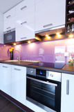 Modern white kitchen with spotlights. Modern white and purple kitchen interior Royalty Free Stock Photos
