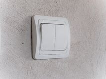 Modern white light switch on gray concrete wall stock photo