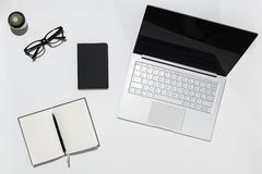 Modern White minimalistic desk table with laptop,, notebook with pen and eyeglasses. Top view with copy space. Working stock image