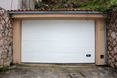 Modern white rollup garage doors with small handle for manual opening mounted on renovated garage wall surrounded with traditional. Stone wall and concrete stock photos