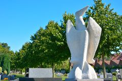 Modern white sculpture of a abstract bird. In the clear blue sky Stock Images
