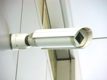 Modern white security camera. On modern facade with window Royalty Free Stock Image