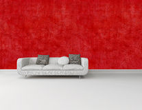 Modern white sofa against a bright red wall Royalty Free Stock Photography