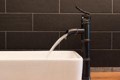 Modern white square sink in bathroom with black tiles and black faucet in shape of bamboo. Modern bathroom design. Interior decoration Royalty Free Stock Images