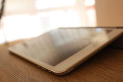 Modern white tablet on the wooden table. Photo of modern white tablet on the wooden table stock photo