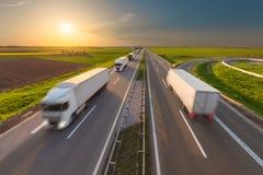 Modern white trucks on highway at idyllic sunset