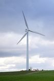Modern Wind Turbine standing on a green field Stock Images