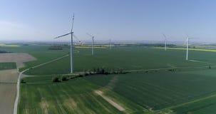 Modern wind turbines generating sustainable energy on field with crop, aerial shot. Modern wind turbines generating sustainable energy on field with crop in slow stock video footage