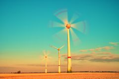 Modern Wind Turbines Producing Energy in sunny spring morning. Vintage Style Toned effect Stock Image