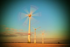 Modern Wind Turbines Producing Energy in sunny spring morning. Vintage Style Toned effect Stock Photo