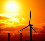 Modern windmill and chimneys of power station at sunrise Royalty Free Stock Photo