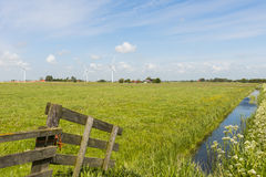 Modern Windmill in Friesland with Ditch. Modern windmills at the horizon in province Friesland near Idsegahuizum, The Netherlands, image Daan Kloeg, Commee Stock Image