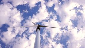 Modern windmill spinning its blades generating electricity with cloud background