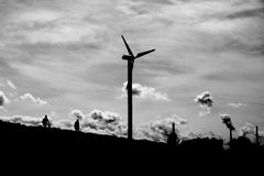 Modern windmill turbine, people walking by. Royalty Free Stock Images